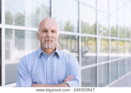 Old  Man Standing With Backdrop Of Business Building