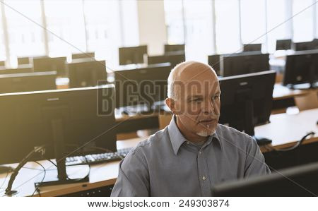 Senior Man Sitting And Working At Computer