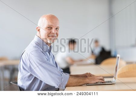 Mature Man Seated And Looking At Camera While Working On On Lapt