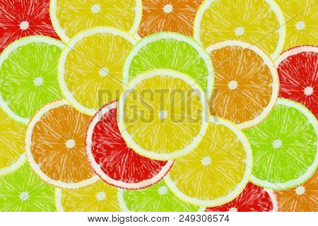 Close-up Of Sliced Multicolored Juicy Citrus Fruits. View From Above To Many Stacked Sliced Fruits.