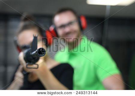 Shooting Range. A Woman Shoots A Rifle. The Woman Shoots From The Gun At The Shooting Range Under Th