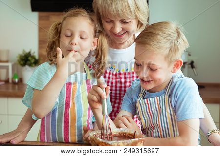 Happy Grandmother With Her Grandchildren Having Fun During Baking Muffins And Cookies