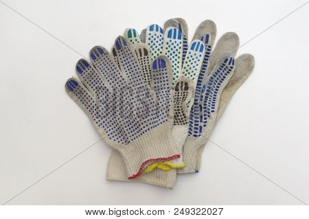 Stack Of Cotton Gloves With Multicolored Rubber Dots, Elastic Cuffs, Bordered By Blue, Red And Yello