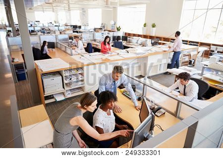 Colleagues working at a woman's workstation in a busy office