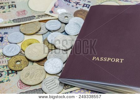 Closeup Of Japanese Yen Banknotes And Japanese Yen Coin With Passport. Financial Money And Travel Co