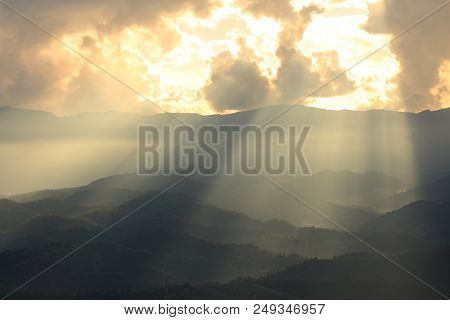 Dramatic God Lights Passing Through Clouds And Shining On Mountain Ranges. Warm Light Shower. God Ho
