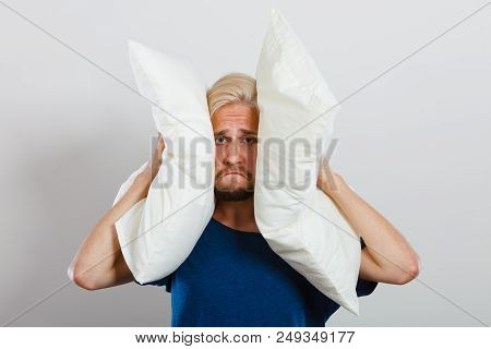 Man Need Silence. Sad Tired Young Male Closing Ears With Pillows, Protecting From Loud Noise, Have H