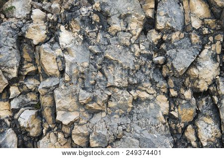 Pebble Stones In A Rocky Wall. Natural Background Of A Rocky Stone Wall.