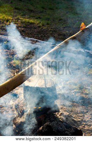 Old School Way Of Making Tea Outdoor. Steam And Smoke All Around. Black Cauldron Hang On The Log Abo