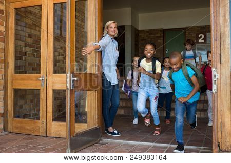 Smiling elementary school children happy to go home. Joyful school girls and boys wearing backpack and running outside the school at the lessons. Teacher holding door while students running out.