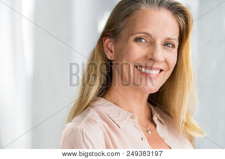 Portrait of mature woman enjoying life after retirement and looking at camera. Closeup face of happy senior woman with blond hair smiling. Beautiful smiling lady indoor.