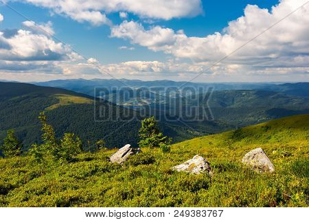 Three Boulders On Grassy Hillside Of Runa Mountain Under The Summer Sky. Fluffy Clouds Over The Polo