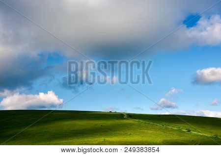 Grassy Hillside And Gorgeous Afternoon Cloudscape. Countryside Road Winds Uphill In To The Distance.