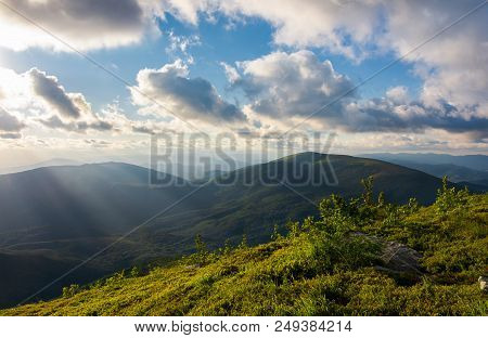 Beautiful Cloudscape Over The Summer Mountains. Grassy Hills And Distant Mountains In Evening Side L