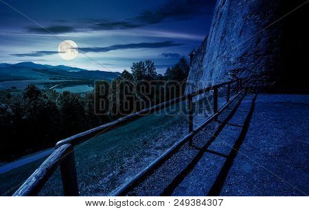 Castle Wall And Railing On A Hill At Night In Full Moon Light. View In To The Beautiful Mountainous