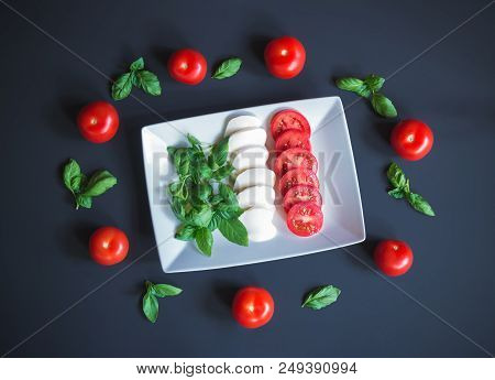 Mozzarella, Tomato, Basil In Form And Color Of Italian Flag On White Plate With Tomatoes And Basil L