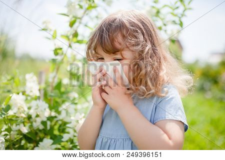 Allergy Concept. Little Girl Is Blowing Her Nose Near Blooming Tree. Allergy To Flowers.