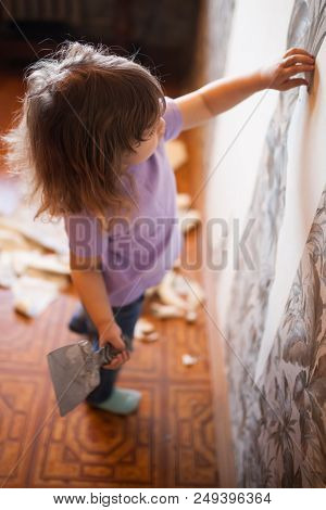 Adorable little girl repairing wall in apartment, holding putty knife old wall at the background. Concept of easy home renovating poster