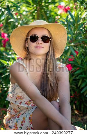 Summertime In Garden. Young Beautiful And Smiling Woman In Garden With Red Flower.