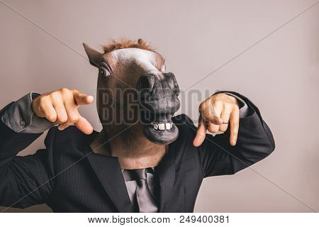 Unidentified Person With A Dark Grey Suit And Tie Wearing A Horse Mask Pointing At The Camera