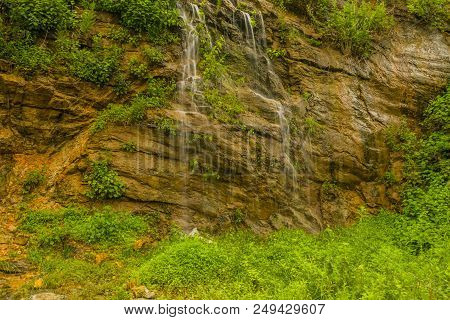 Beautiful Natural Waterfall Cascading Down Mountain Hillside Of Rocks And Lush Green Foliage,