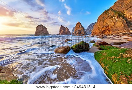 Portugal Ursa Beach at atlantic coast of Atlantic Ocean with rocks and sunset sun waves and foam at sand of coastline picturesque landscape panorama. Stones with green moss.