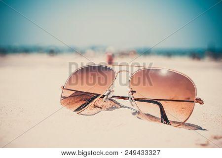 Vintage photo of nostalgia in summer - sunglasses on sand beach. retro film filter effect poster
