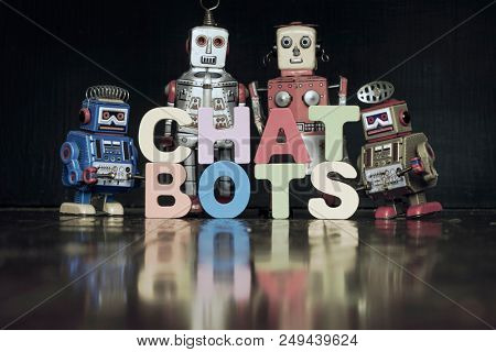 the word  CHAT BOTS with rtro robots on a wooden floor with reflection toned