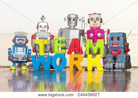 the word TEAM WORK  with wooden letters and 5 retro bots on a wooden floor