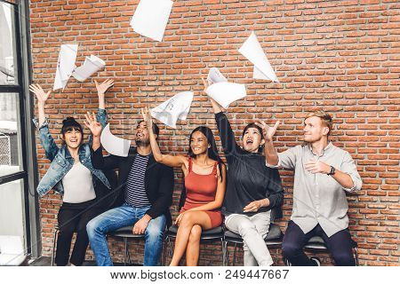 Successful Group Of Casual Business Relaxing And Throwing Paper In Modern Work Loft.creative Busines