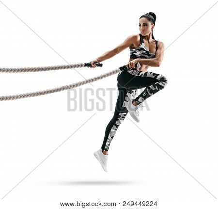 Muscular Woman Jumping With Heavy Ropes. Photo Of Latin Woman In Military Sportswear Isolated On Whi