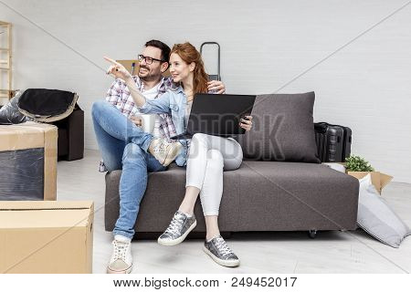 Young Couple Sitting In New Empty Room With Unpacked Boxes And Looking At Laptop While He Drink Cofe