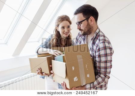 In New Empty Appartment Young Couple Carrying Unpacked Boxes