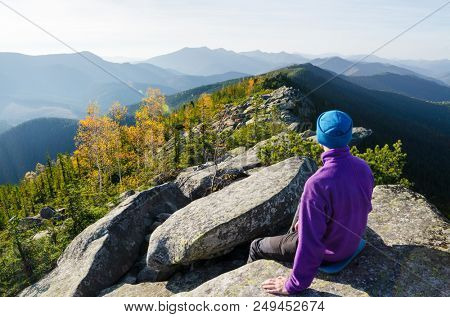 Guy on a mountain ridge contemplates nature. Autumn landscape on a sunny morning. Tourist in the hike