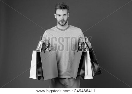 Man With Shopping Bags On Violet Background. Macho With Colorful Paper Bags. Fashion Shopper In Casu