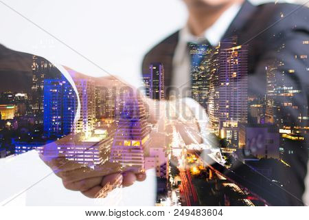 Double Exposure Concept. Investor Business Handshake With City Night. Businessman Shaking Hands Usin
