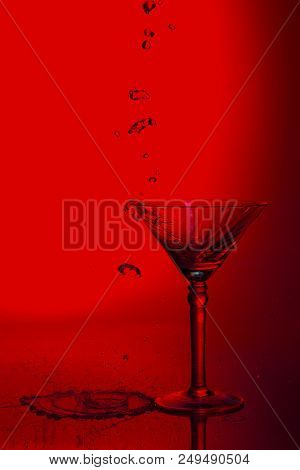 Martini Glass High Key Photo In Studio With A Red Tint And Water Plash