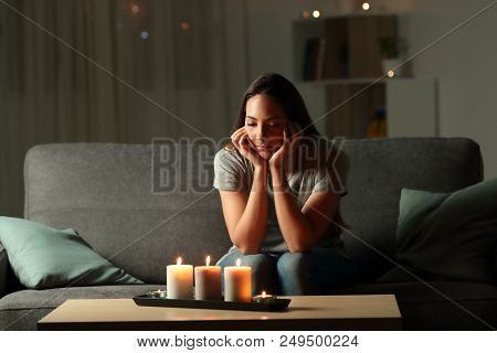 Distracted Woman Looking At Candles Light During Blackout Sitting On A Couch In The Living Room At H