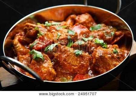 Indian chicken jalfrezi curry. Shallow DoF, focus on central chicken piece.