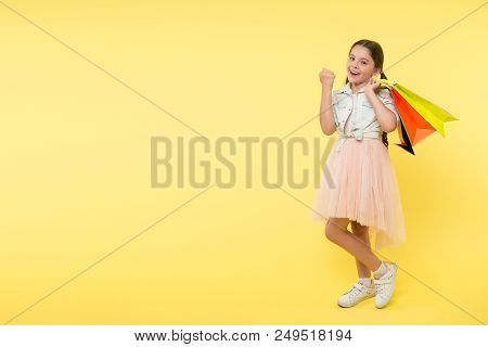 Girl With Paper Bag. Paper Bag In Hand Of Little Shopaholic. Happy Child Hold Paper Bag. Many Paper