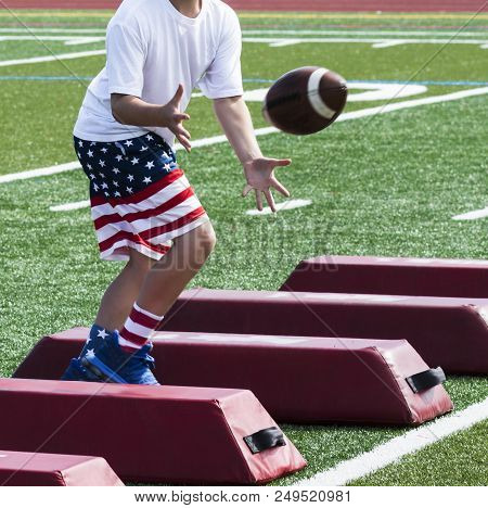 A Young Boy Is At Summer Football Camp Catching A Football While Running Sideways Over Red Barriers