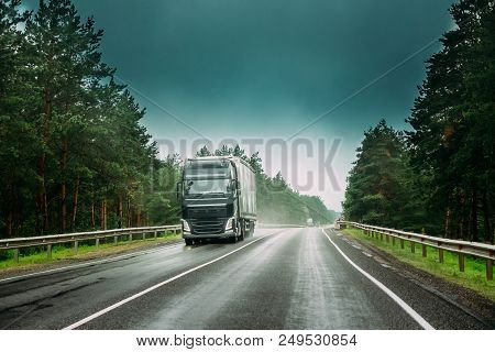 Black Truck Or Tractor Unit, Prime Mover, Traction Unit In Motion On Road, Freeway. Asphalt Motorway