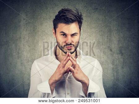 Young Man Holding Hands Together And Looking At Camera With Thoughts Of Revenge And Jealousy