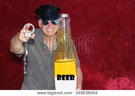 PHOTO BOOTH. A man wears a Police Hat, Holds Hand Cuffs, A Giant Beer Bottle and smiles for his picture in a Photo Booth with a red velvet background.