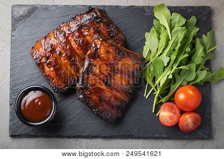 Closeup Of Pork Ribs Grilled With Bbq Sauce And Arugula. Tasty Snack To Beer On A Stone Board For Fi