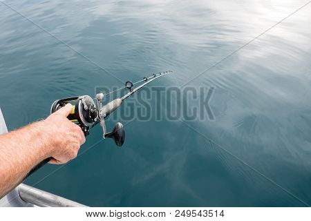 Anticipation Of Catching A Fish: Man's Hand Holding Fishing Rod Pole With Line In Water In Far North