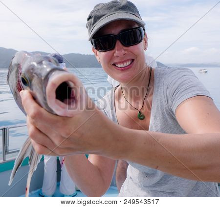 Mature Female Caucasian Tourist Smiling Holding Porae Fish Caught On Fishing Charter Boat In Far Nor