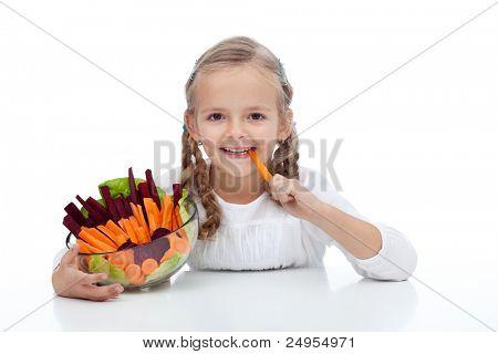 Little girl munching on a carrot stick holding bowl of vegetables