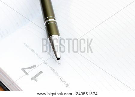 Closeup Of Pen Lying On Open Organizer Or Calendar On Desk In Office