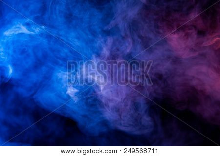 Thick Colorful Smoke Of Blue And Purple On A Black Isolated Background. Background From The Smoke Of
